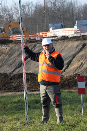 Man on construction site holding pole photo