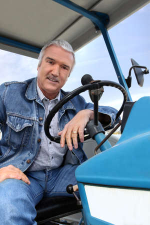 field glass: Man driving a tractor Stock Photo