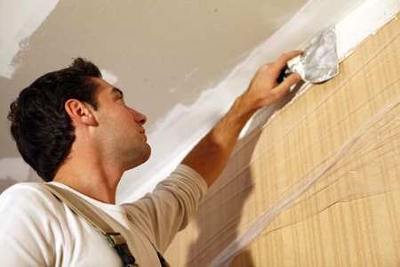 plasterboard: Man putting up a plasterboard ceiling