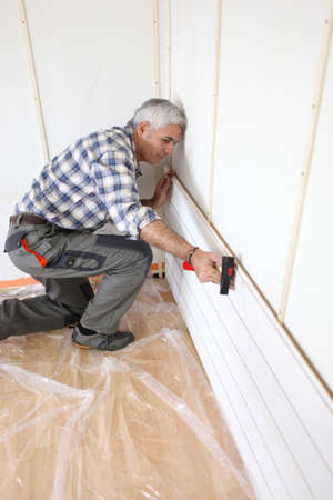 tongue and groove: Man putting up interior wood cladding