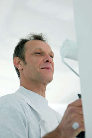 fulfilling: Happy man using a paint roller Stock Photo