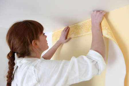 facelift: Woman putting up a wallpaper border