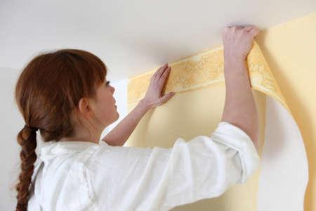 refurbish: Woman putting up a wallpaper border