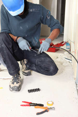 mucky: Electrician wiring a house Stock Photo