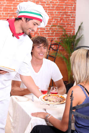 young couple eating pizza in a restaurant photo