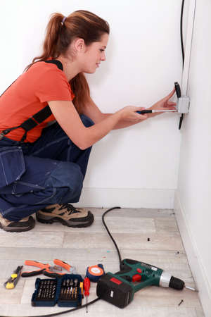 25 30 years women: Electrician installing an electrical outlet Stock Photo