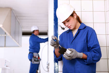 Male and female electricians working together Stock Photo - 11610698
