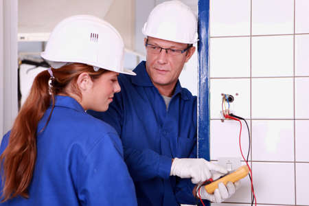 jumpsuite: an electrician teaching how to use an ammeter Stock Photo