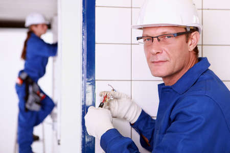 tiled wall: Electrician wiring a wall socket