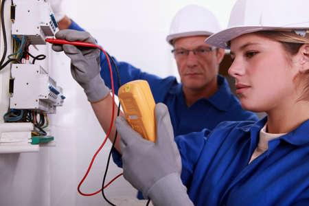 contador electrico: Tradeswoman con un multímetro