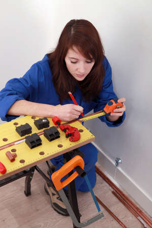 carpenter vise: A female, plumber taking measures.