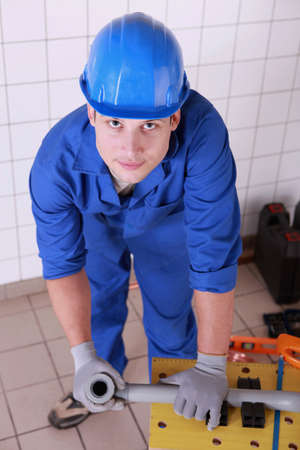 Plumber preparing to cut piece of pipe Stock Photo - 11606105