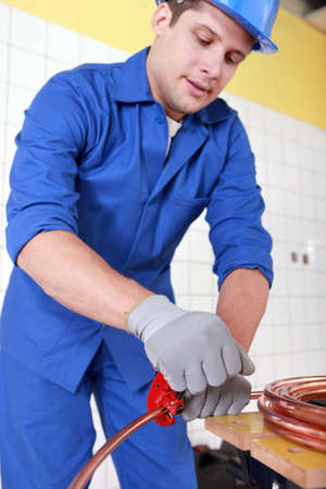 plumbing accessories: Plumber cutting copper pipe