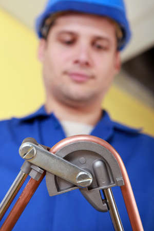 condensing: Plumber bending copper pipe Stock Photo
