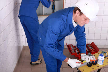 exactitude: Plumbers working in a tiled room