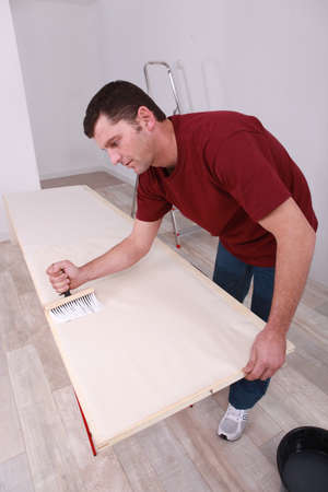 pegamento: El hombre pegar papel tapiz Foto de archivo
