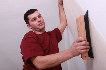 Low shot of a man smoothing wallpaper with a large brush photo