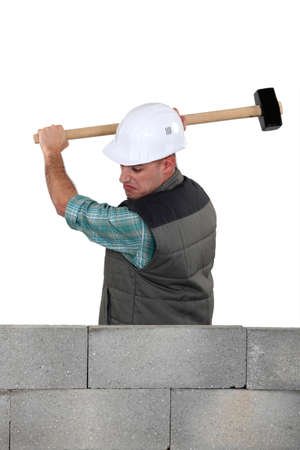 sledge hammer: Man hitting a wall with a sledgehammer Stock Photo