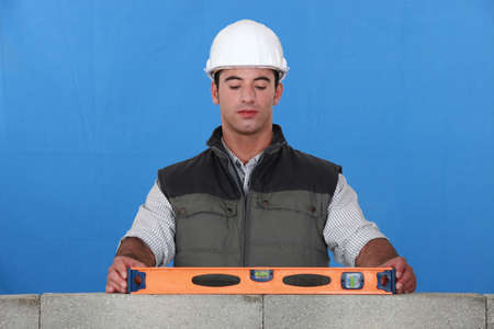Bricklayer with a spirit level photo
