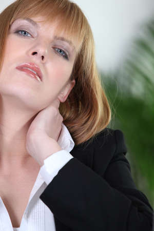 grabbing at the back: woman with cervical pain
