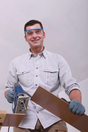 Smiling handyman cutting planks photo