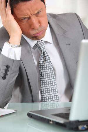 45 49 years: Perplexed man in suit staring at laptop computer Stock Photo