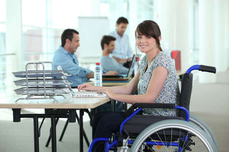 Woman in wheelchair with laptop computer photo