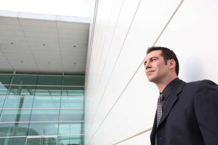 well dressed man leaning against a modern building Stock Photo - 11605646