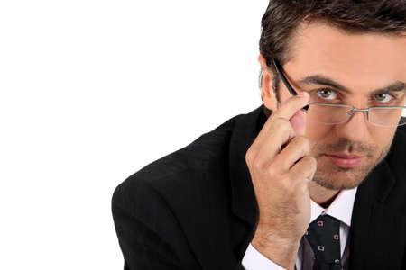 authoritative: Well dressed man touching glasses