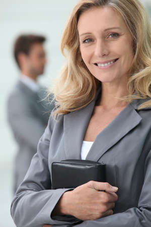 Smiling businesswoman holding personal organiser with colleague in background photo