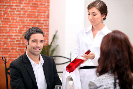 alcohol server: Sommelier presenting a wine to a restaurant patron Stock Photo