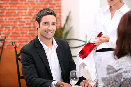 Waitress bringing wine to customer photo
