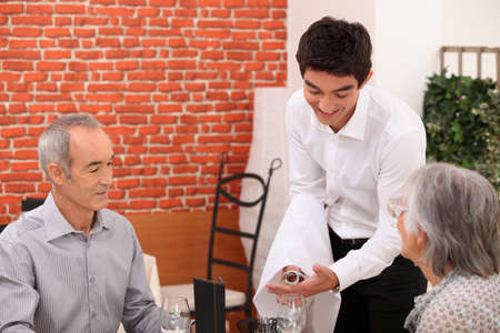 alcohol server: Young waiter pouring wine for an older couple