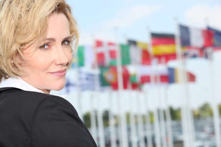 business trip: Businesswoman next to flags
