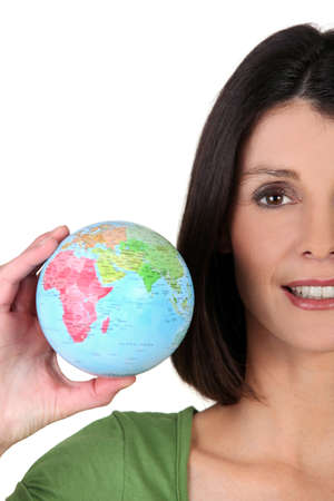 foreign policy: young woman taking a little globe in her hand