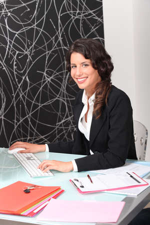 Female estate agent working at desk photo