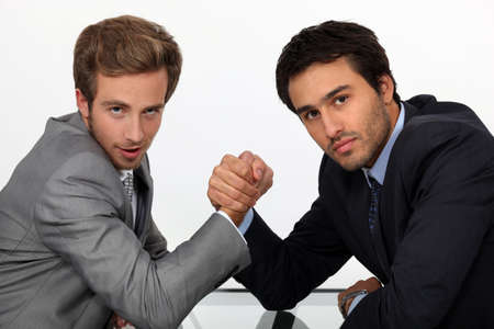 two young men well dressed doing arm-wrest photo
