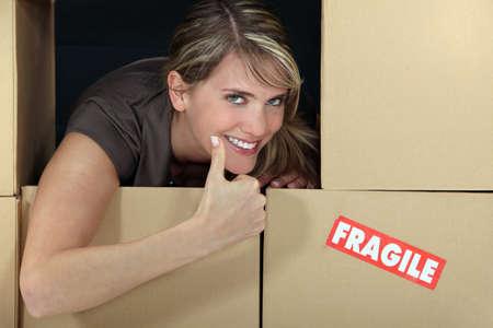 amongst: Woman stood amongst fragile boxes
