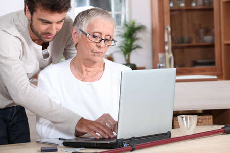 Young man helping a senior with a laptop computer photo