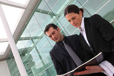 Ceo and assistant standing outdoors photo