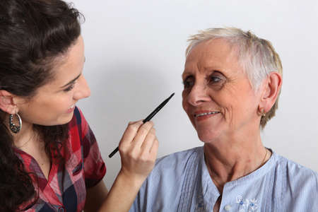 Young woman applying makeup to an elderly lady Stock Photo - 11612403