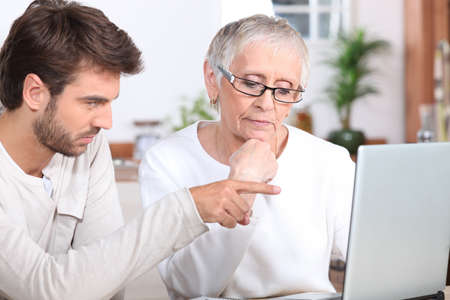 Young man showing a senior woman how to use a laptop photo