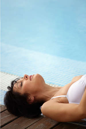 Brunette having a nap by swimming pool Stock Photo - 11605602