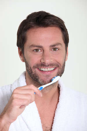 Good looking mature man brushing his teeth in the morning photo