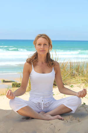40 45: Woman meditating on the beach Stock Photo