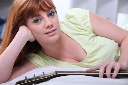 Girl in bedroom with guitar photo