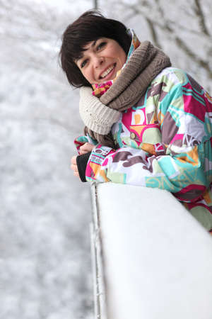 powdery: Woman leaning against a snow-covered ledge
