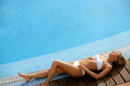Gorgeous woman laid at the poolside photo