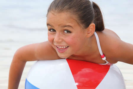 Little girl playing with beach ball photo