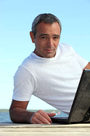 A mature man with his laptop by the seashore. photo